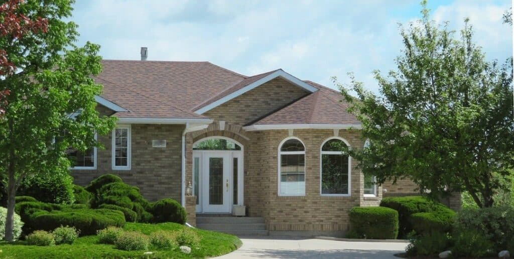 a suburban brick home with a brown roof